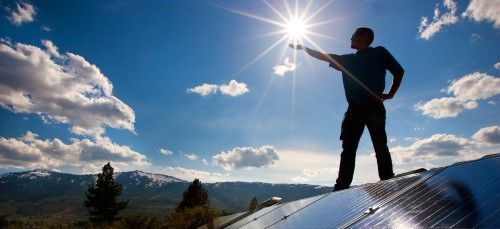 Daniel Herr standing about a Solar Photovoltaic Array holding the Sun in his hand.