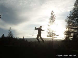Andrew Herr jumping on the golf course at Martis Camp with Sunset in Tree